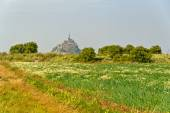 View across lush rural fields to Mont St Michel — Stock Photo