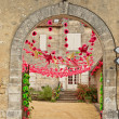 Stone archway with colorful red bunting — Stock Photo #65074423