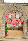 Stone archway with colorful red bunting — Stock Photo
