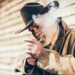 Senior man lighting up his cigarette — Stock Photo #72500251