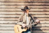 Gitarzysta opierał się na ścianie drewniany dom — Zdjęcie stockowe