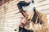 Senior man lighting up his cigarette — Stock Photo