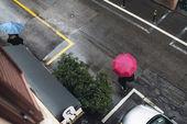 Persona che utilizza l'ombrello rosso che attraversa una strada — Foto Stock