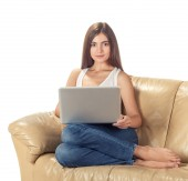 Happy pretty woman using laptop sitting on cosy sofa — Stok fotoğraf