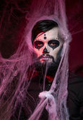 Halloween concept with young man in day of the dead mask face art. — Stockfoto