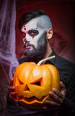 Halloween concept with young man in day of the dead mask face art — Stockfoto