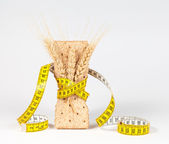 A yellow measuring tape wrapping wheat cracker or crispbread and sheaf of wheat - healthy eating concept — Stock Photo