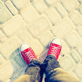 Young man feet in red sneakers on cobbled road — Stock Photo
