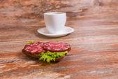 Frukost med salami smörgås och kopp te — Stockfoto