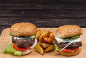 Hamburger and french fries on a wooden plate — Stock Photo