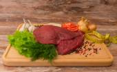 Raw beef meat with vegetables on wooden plate. — Stock Photo