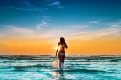 Woman in white bikini posing in a sea at sunset — Stock Photo