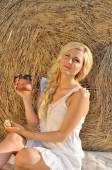 Happy woman posing with bread, milk and hay — Stock Photo