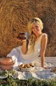 Happy woman posing with bread, coffee cup and hay — Stock Photo