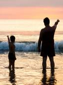 Father and son in front of evening sky seaside — Stock Photo