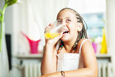 Young girl drinking orange juice — Stock Photo