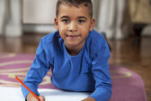 Young mixed race boy drawing on paper with crayon. — Stock Photo
