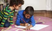 Young mixed race boys drawing on paper with crayon. — Stock Photo