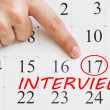 Interview date is circled on a calendar page with a finger pointing on it — Stock Photo #58884211