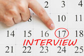 Interview date is circled on a calendar page with a finger pointing on it — Stock Photo