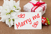 Marry Me! written in a greeting card with a beautiful flowers and a gift box — Stock Photo