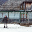 MAGURA, ROMANIA - 05 FEB: Old romanian peasant in front of his old house on February 05 2015. Magura is a village in Carpatian Mountain — Stock Photo #64367805