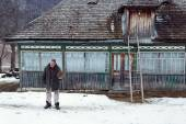 MAGURA, ROMANIA - 05 FEB: Old romanian peasant in front of his old house on February 05 2015. Magura is a village in Carpatian Mountain — Stock Photo