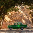 Classic old car under trees in Cuba — Stock Photo #68575625