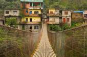Rope hanging suspension bridge in Nepal with colorful village in — Stock Photo