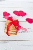 Some cookies hearts tied with red ribbon — Stock Photo