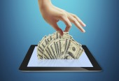 Tablet showing financial symbols coming — Stock Photo