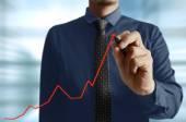 Businessman hand writing a business graph — Stockfoto
