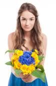 Jeune modèle féminin offrant un bouquet de fleurs — Photo
