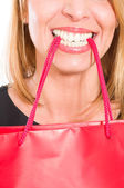 Sopping woman holding bag with her teeth — ストック写真