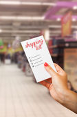 Woman hand holding shopping list — Stock Photo