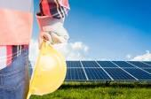 Engineer holding hardhat on solar power photovoltaic panels back — Stock Photo