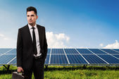 Salesman or businessman holding briefcase on solar power panels — Stock Photo