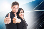 Happy couple showing like on solar power photovoltaic panel back — Stock Photo