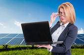 Businesswoman with solar power plant in background — Stock Photo