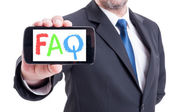 FAQ or frequently asked questions on smartphone hold by business — Stock Photo