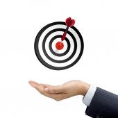 Businessman's hand holding target button — Stock Photo