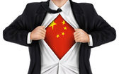 Businessman showing China flag underneath his shirt — Stock Vector