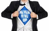 Businessman showing Never give up words underneath his shirt — Stock Vector