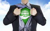 Businessman showing earth icon underneath his shirt — Stock Photo