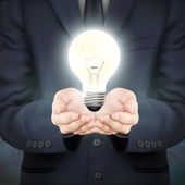 Businessman holding lighting bulb — Stock Vector