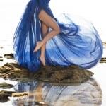 Long blue dressed slim woman legs at the beach — Stock Photo #52837061