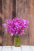 Beautiful bouquet of orchids flower on a wooden background — Stock Photo