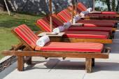 Sun loungers with towels near the swimming pool — Stock Photo