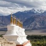 Buddhist chortens (stupa) and Himalayas mountains in the background near Shey Palace in Ladakh, India — Stock Photo #70062515
