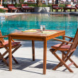 Table and chairs in empty cafe next to the pool — Stock Photo #70105001